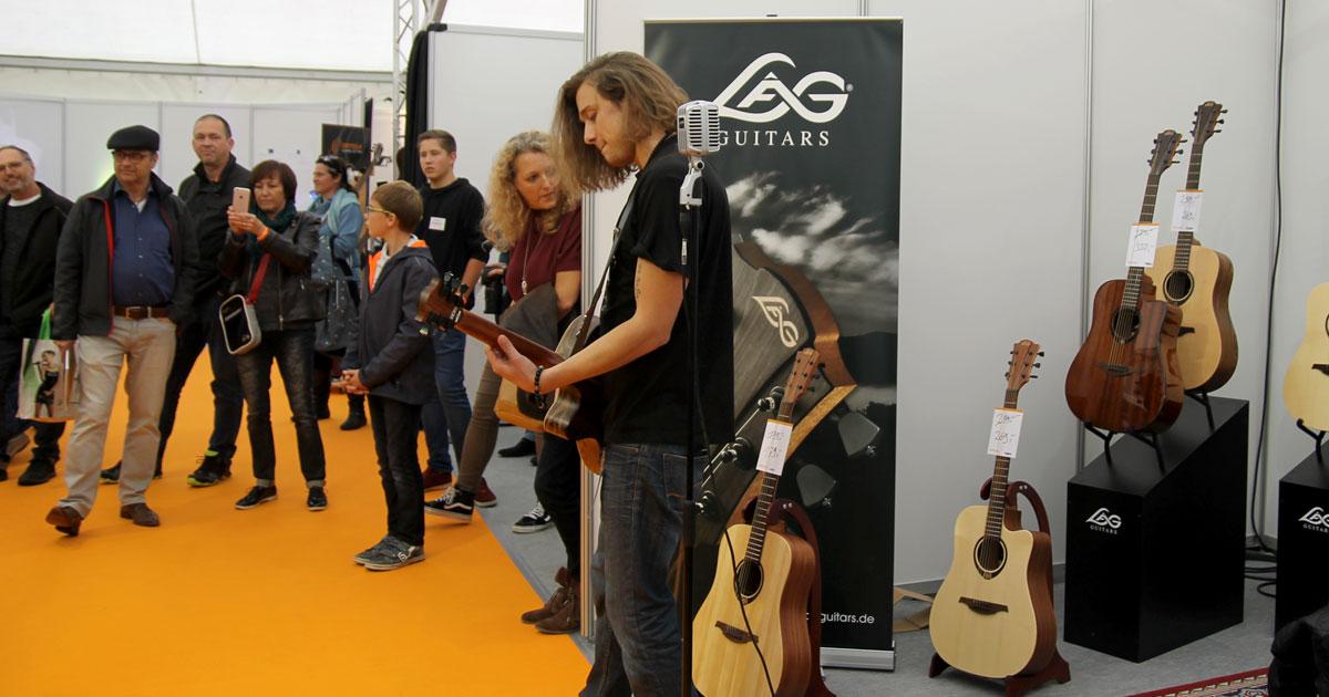Sebastian Dracu am Stand von Lag Guitars im Messezelt