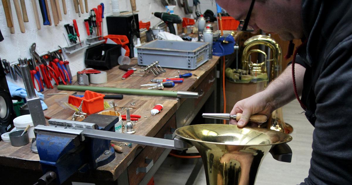 Arbeiten mit einer Sichel: Dellen am Schallstückrand dieses Baritons werden entfernt, der Rand wird geglättet.