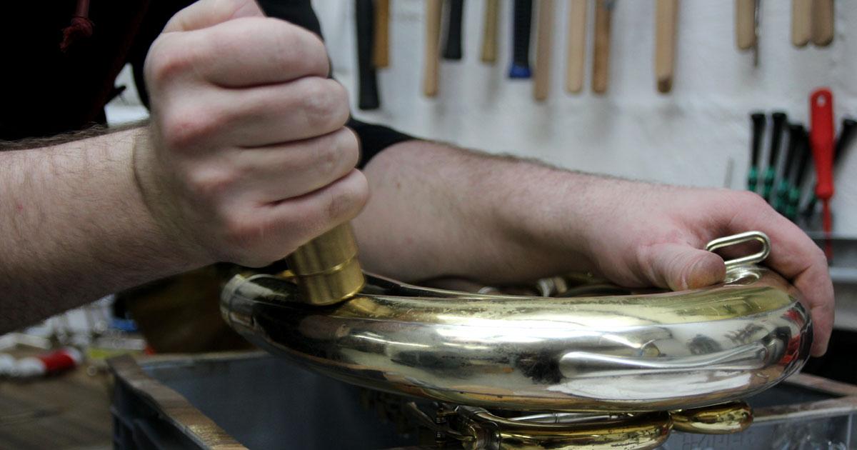 Mit Hilfe einer Eisenkugel und eines Magneten beult Frank das Bariton an mehreren schwer zugänglichen Stellen aus.