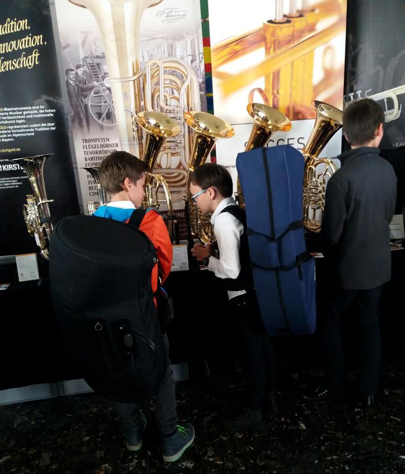 Junge Musiker bestaunen Blasinstrumente am Kirstein-Ausstellungsstand beim Bezirksmusikfest in Hohenfurch