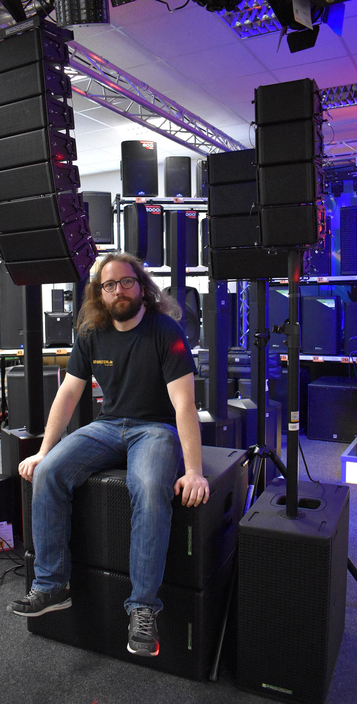 Ruben aus dem Kirstein-Team, sitzend auf Subwoofern, die zum Pronomic V-Array-System gehören.