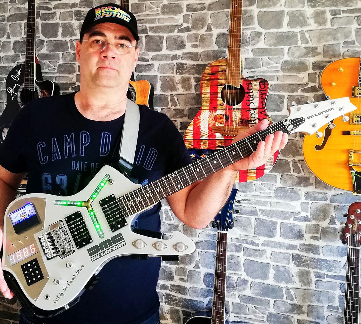 Thomas mit der von ihm umgebauten Gitarre im Back-to-the-Future-Design. Im Hintergrund sieht man weitere außergewöhnliche Gitarren an der Wand hängen.