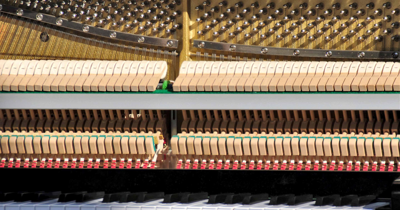 Oberhalb der Mechanik sieht man die aus Metall gefertigten Stimmwirbel des Klaviers.