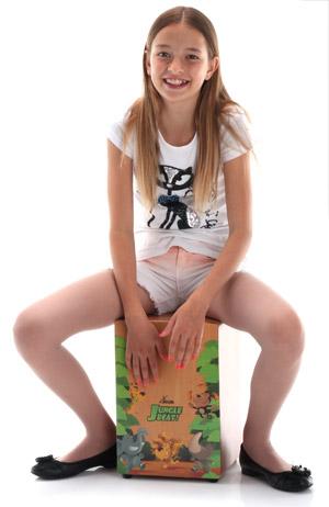 Ein Mädchen spielt fröhlich auf der XDrum Jungle Beat Kinder-Cajon. Foto © Musikhaus Kirstein GmbH.