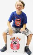 Junge sitzt auf selbst gefalteter und bemalter Cajon und trommelt